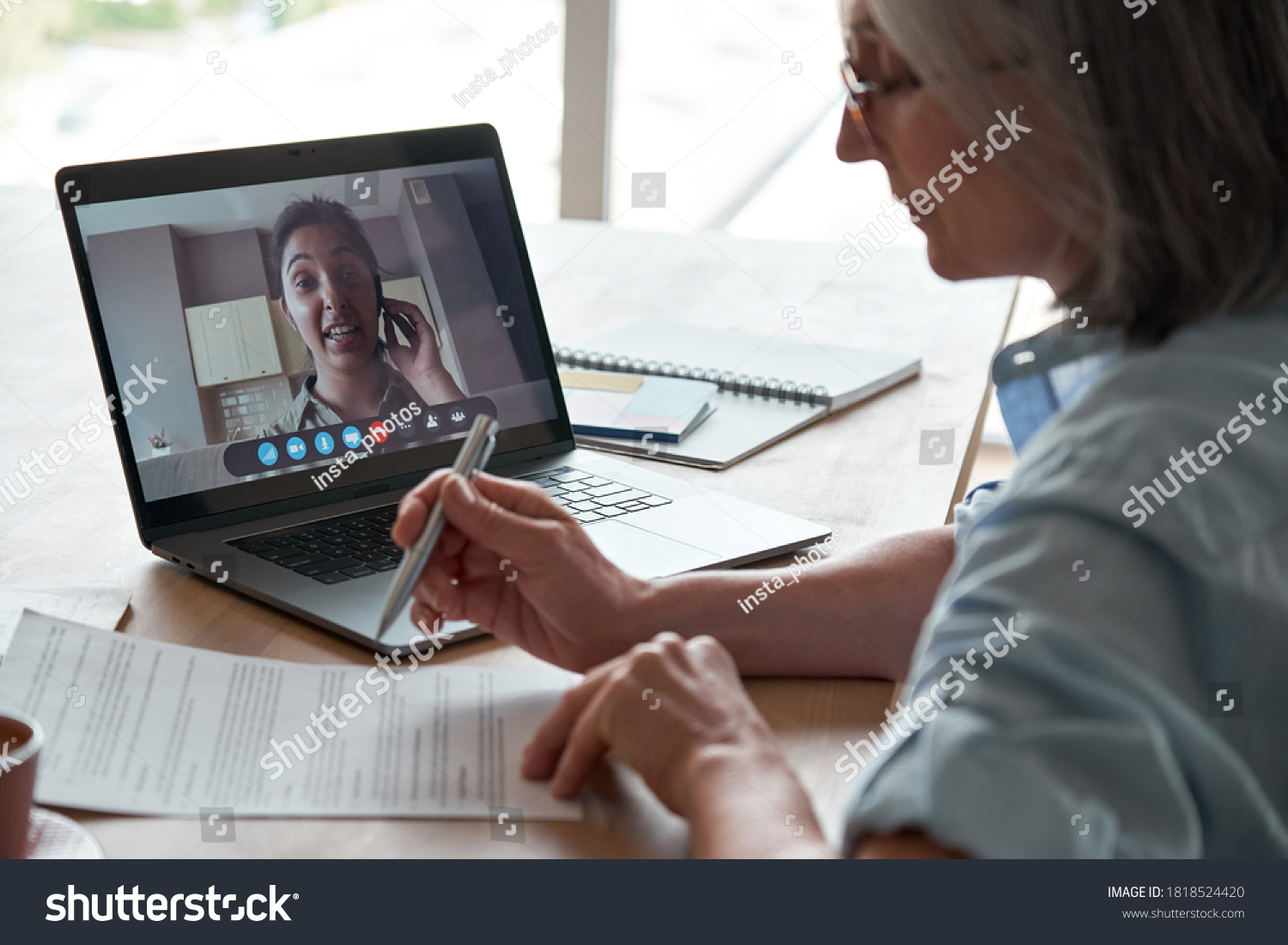 Old hr employer checking indian female job applicant cv resume by video conference call interview on laptop. Senior client reading insurance contract with virtual lawyer advisor at online legal advice #1818524420