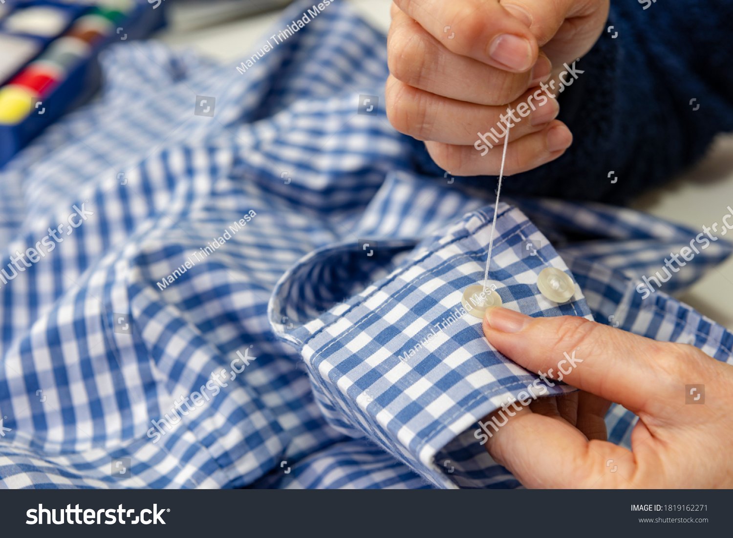 stock-photo-seamstress-sewing-a-button-t