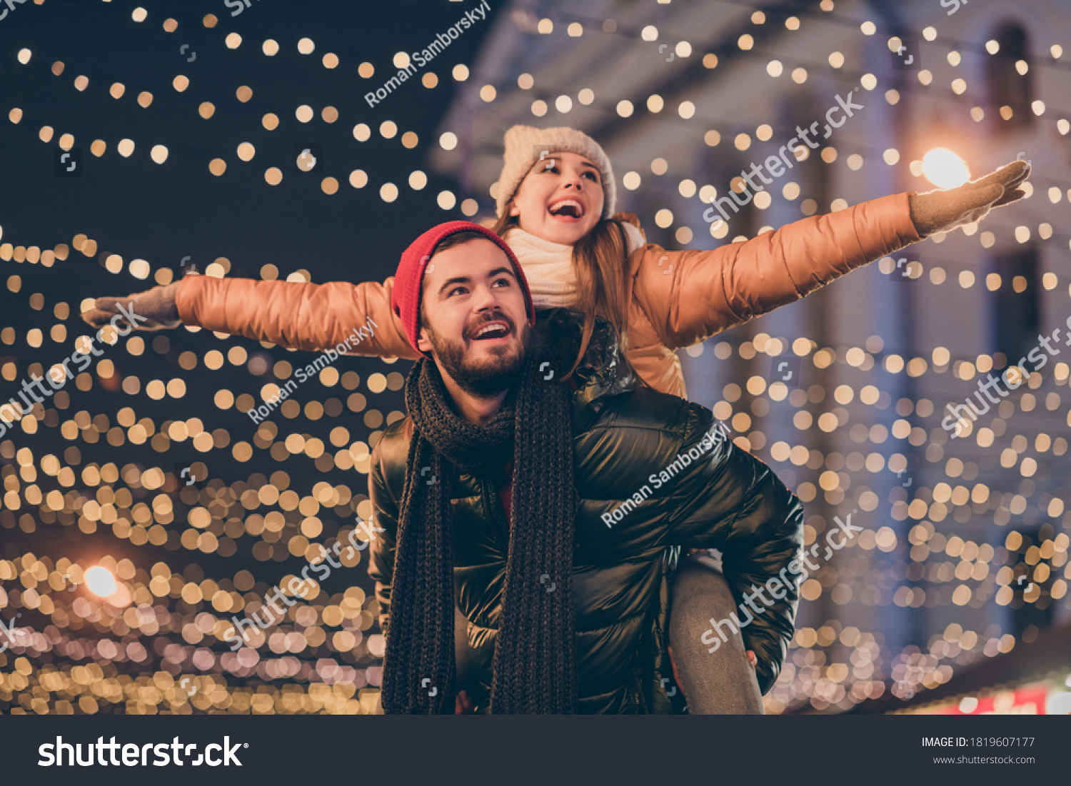 Photo of positive couple having fun christmas x-mas around evening outside illumination boyfriend piggyback girlfriend holding hands fly #1819607177