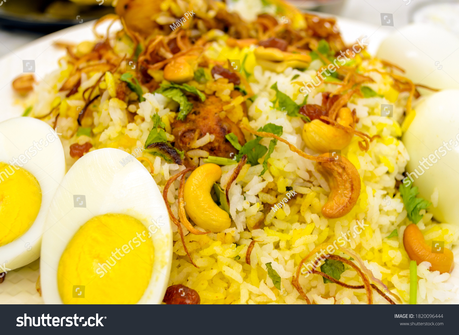 Closeup of chicken biryani plate with cut eggs in the foreground with fried onions and cashew nuts spread on