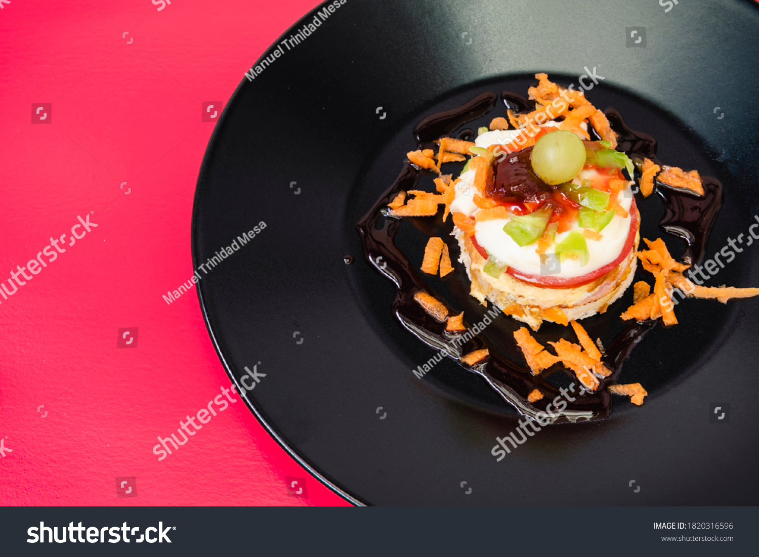 Appetizer based on fresh cheese with fish, fruits and vegetables, decorated on a black plate and red tablecloth