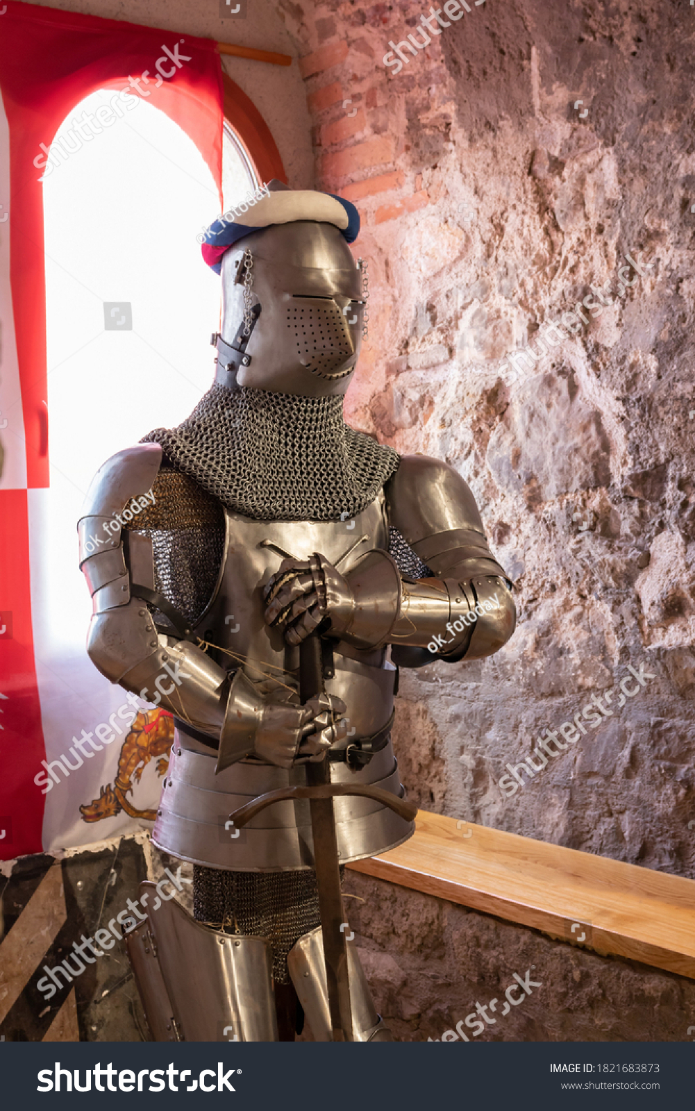 A sample of forged armor of a knight with a sword in chain mail and a helmet in the museum hall in the Golubac fortress. Serbia, Golubac, 13 September 2020