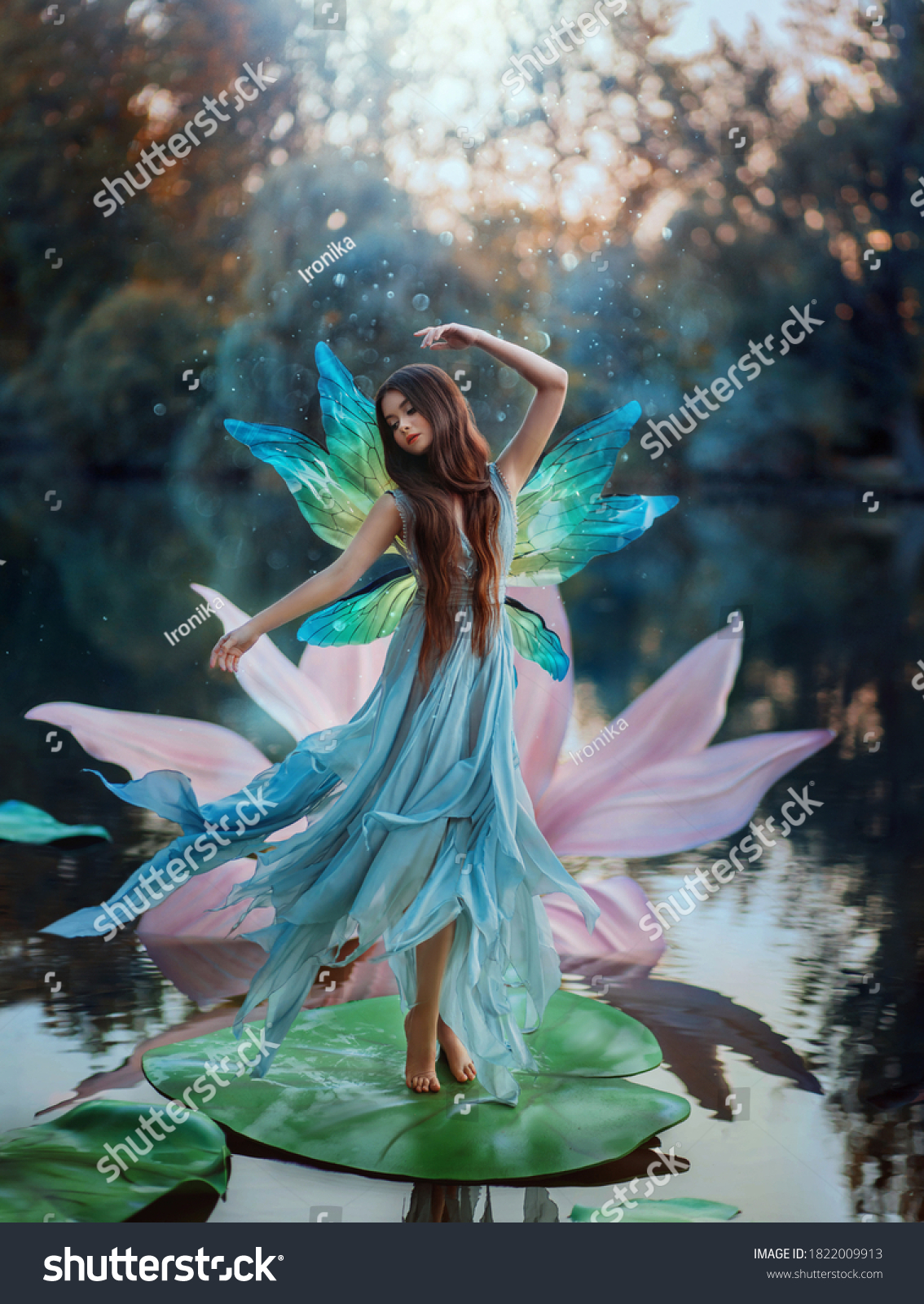 Beautiful young fantasy woman in image river fairy dances on water pink lily flower. long silk dress flies in wind motion butterfly wings magic shiny. Art Girl pixie. Background dark nature, blue lake #1822009913
