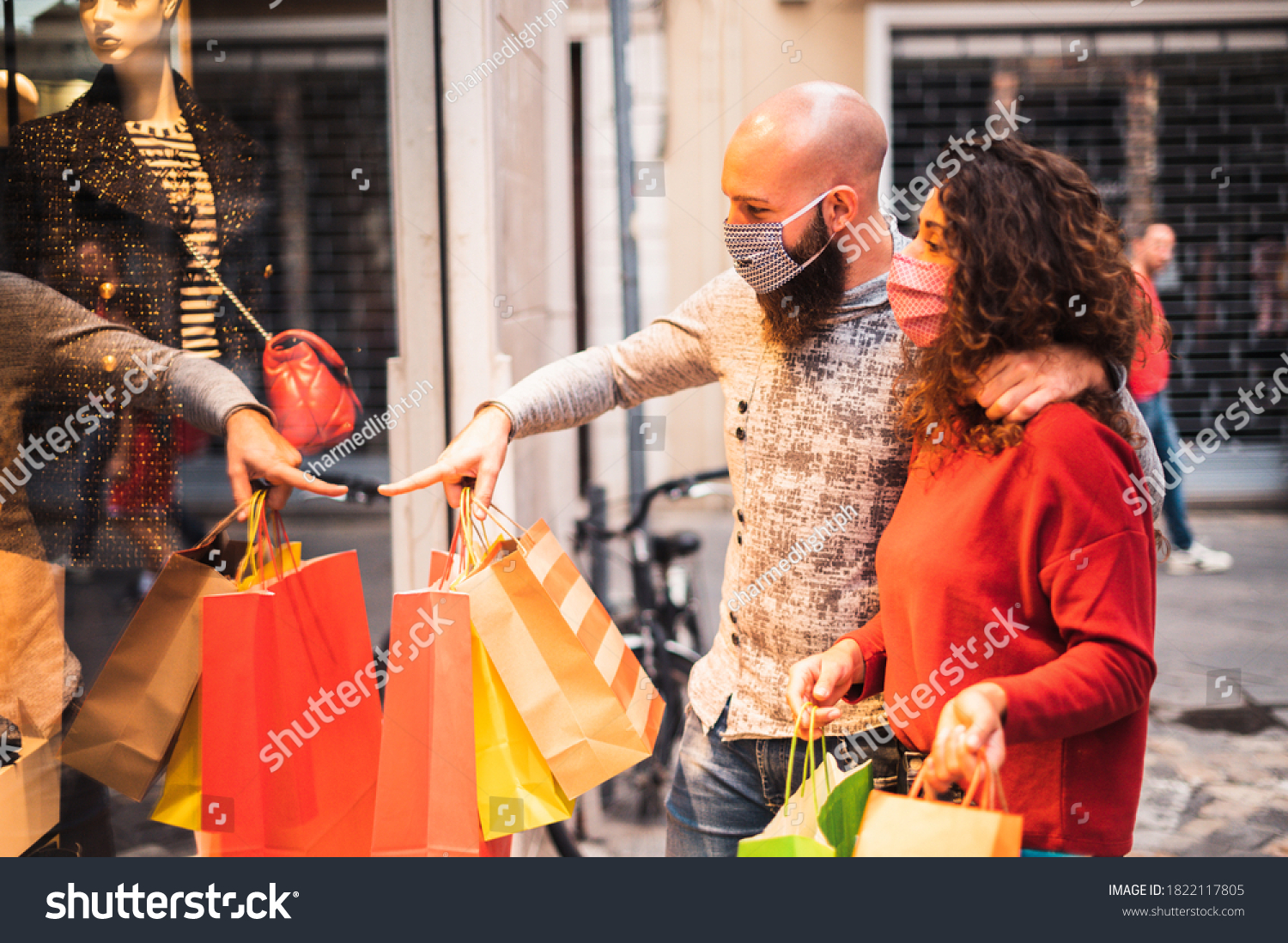 Pretty young man pointing to shop window to show clothing item his likes to his girlfriend - Beautiful young couple enjoying in shopping, having fun together, with the face mask -  #1822117805