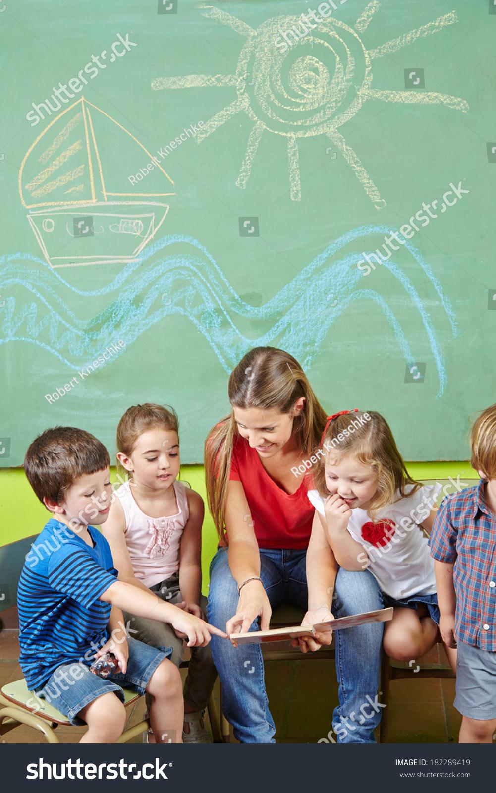 Children In Preschool Reading Book Together With A Nursery Teacher