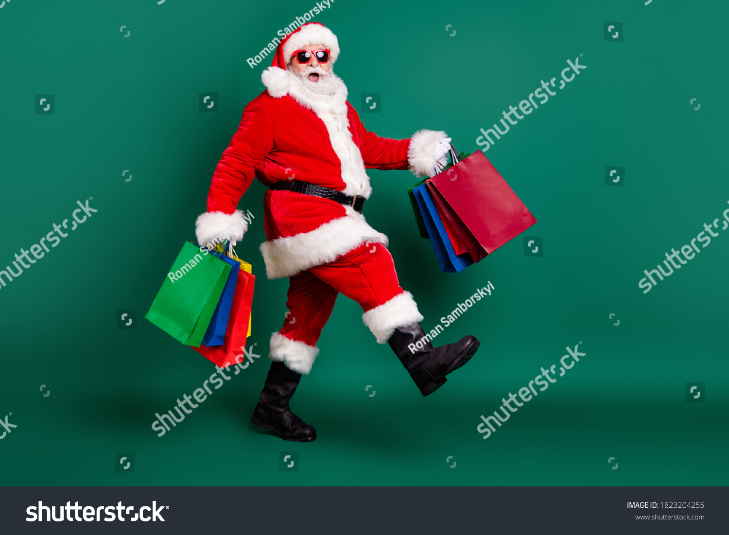 Full length body size profile side view of his he nice fat overweight cheerful glad Santa carrying bags Eve Noel gifts presents surprise festive newyear tradition isolated over green color background #1823204255