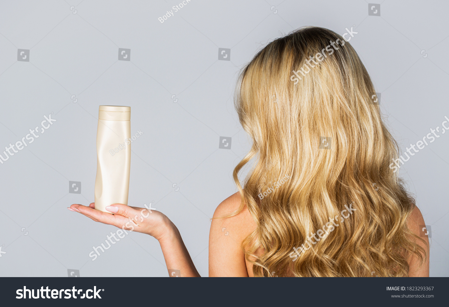 Woman hold bottle shampoo and conditioner. Woman holding shampoo bottle. Beautiful blonde girl with a bottle of shampoos in hands. Girl with shiny and long hair. Woman long hair. #1823293367