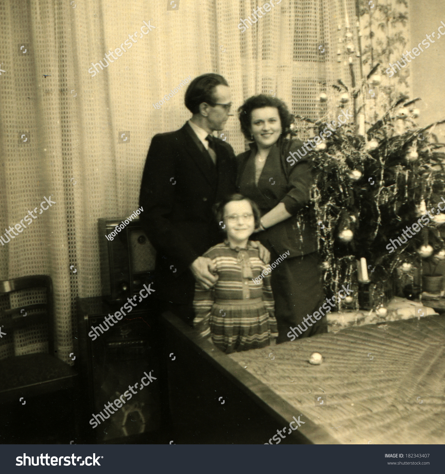 GERMANY - CIRCA 1950s: An antique photo of parents posing with his daughter  near Christmas