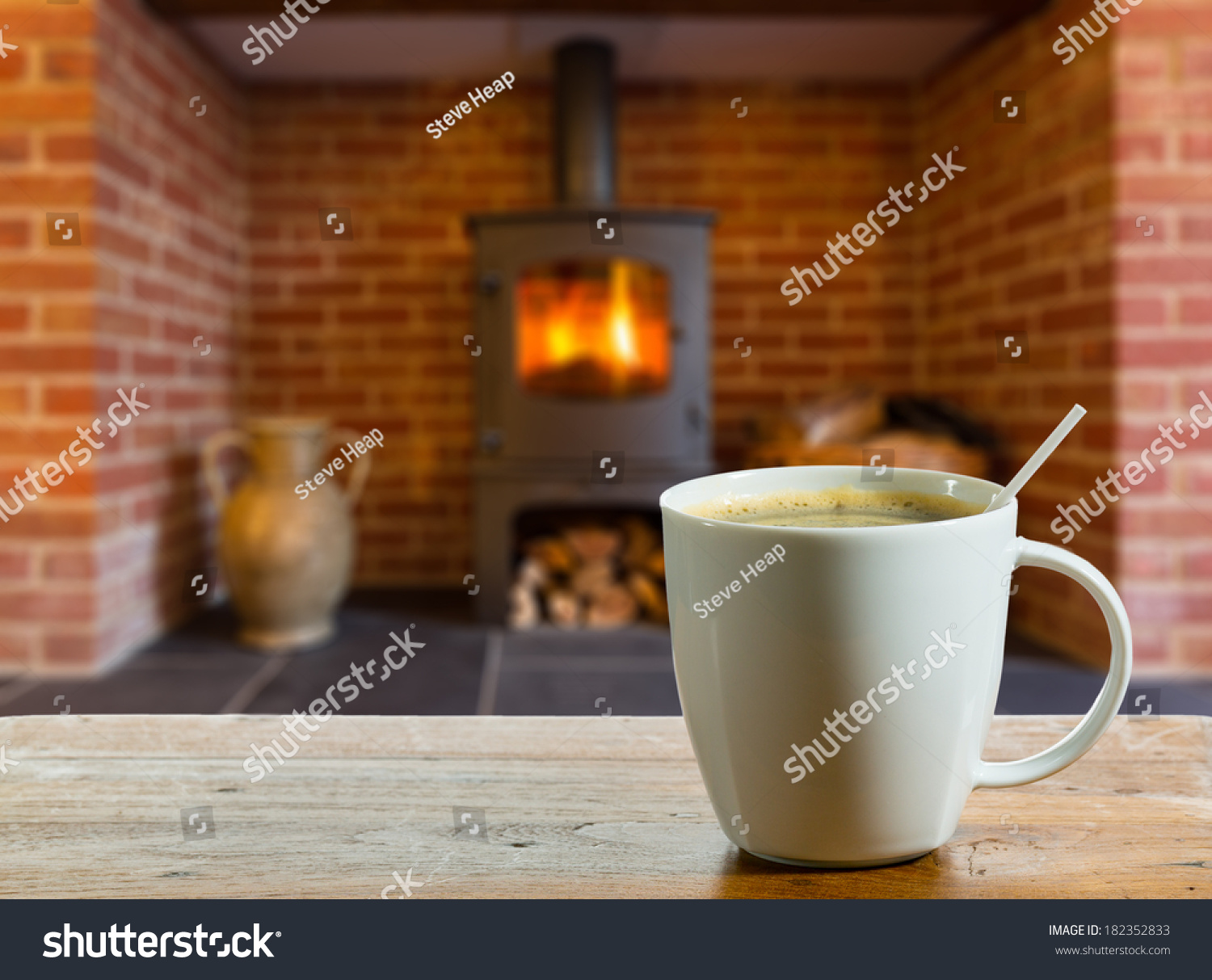 Coffee cup on wooden table front stock photo 182352833 shutterstock coffee cup on wooden table in front of roaring fire inside wood burning stove in brick geotapseo Gallery