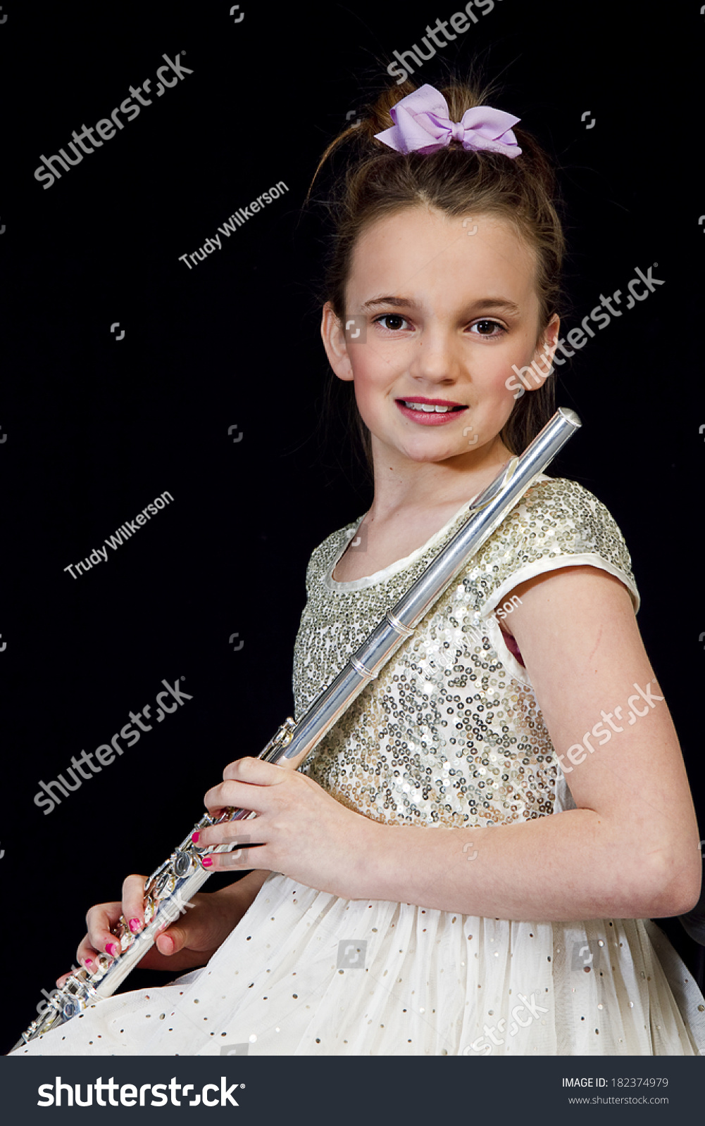 black preteen Young preteen girl playing her flute against black background