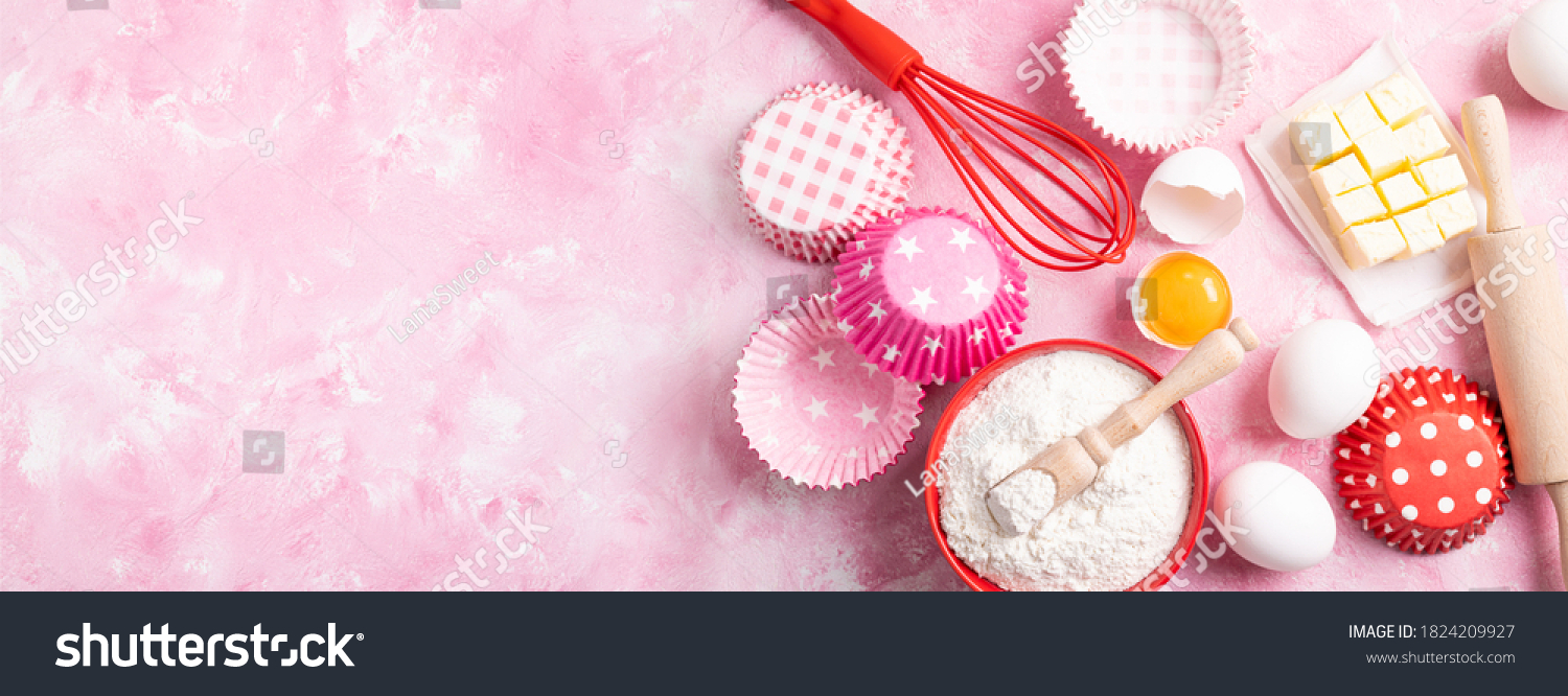 Baking background. Food ingredients for baking flour, eggs, sugar on pink background flat lay. Baking or cooking cakes or muffins. Long format with copy space. Top view #1824209927