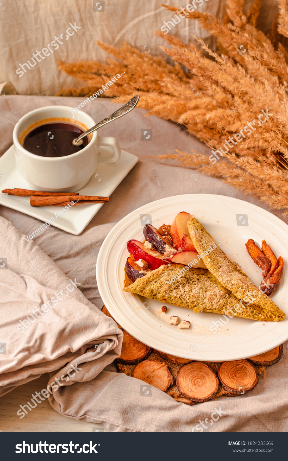 gluten-free keto crepes with peach and almonds and sweet berries. a cup of coffee with cinnamon. selective focus. autumn healthy breakfast or dessert concept. #1824233669