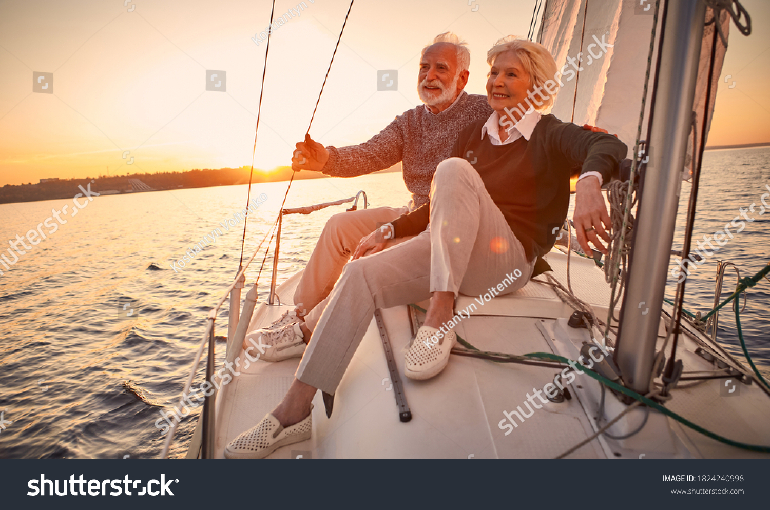 Beautiful and happy senior couple in love sitting on the side of sailboat or yacht deck floating in sea at sunset and enjoying amazing view, sailing together #1824240998
