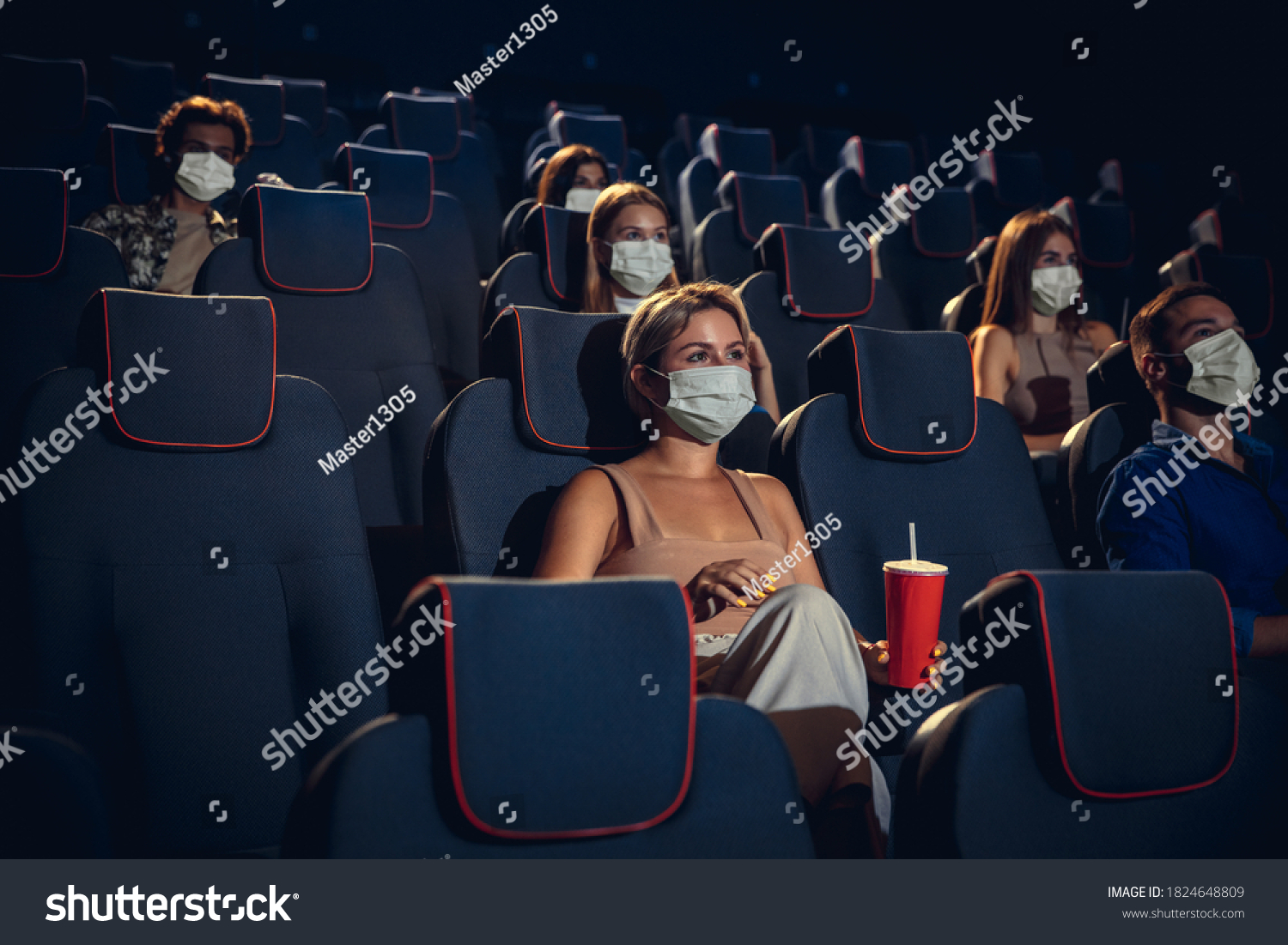 Cinema in quarantine. Coronavirus pandemic safety rules, social distance during movie watching. Men, women in protective face mask sitting in a rows of auditorium. Leisure time, youth culture concept. #1824648809