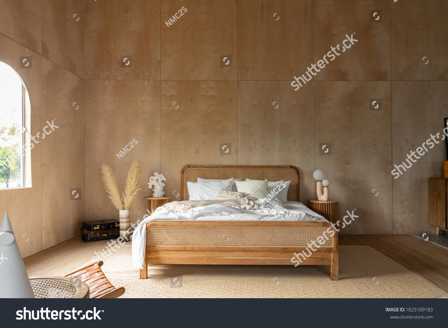 Stylish Bedroom corner with rattan headboard and bed with soft pillows setting with white pillows plywood wall on the background / cozy interior design / modern interior #1825109183