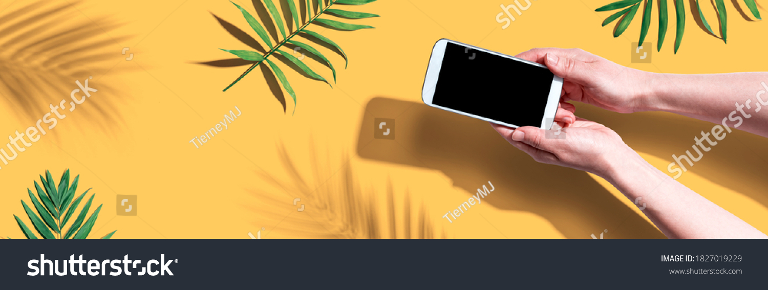 Smartphone with tropical palm leaves and shadow - flat lay #1827019229
