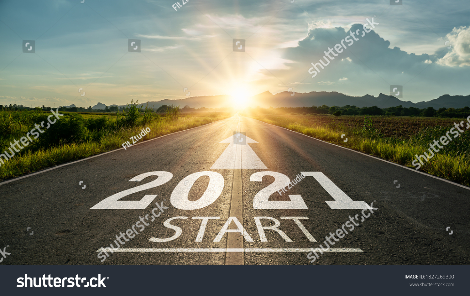 New year 2021 or start straight concept.word 2021 written on the road in the middle of asphalt road at sunset.Concept of planning and challenge or career path,business strategy,opportunity and change #1827269300
