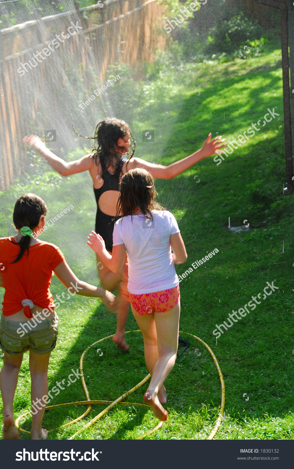 young girls running through sprinkler backyard stock photo 1830132