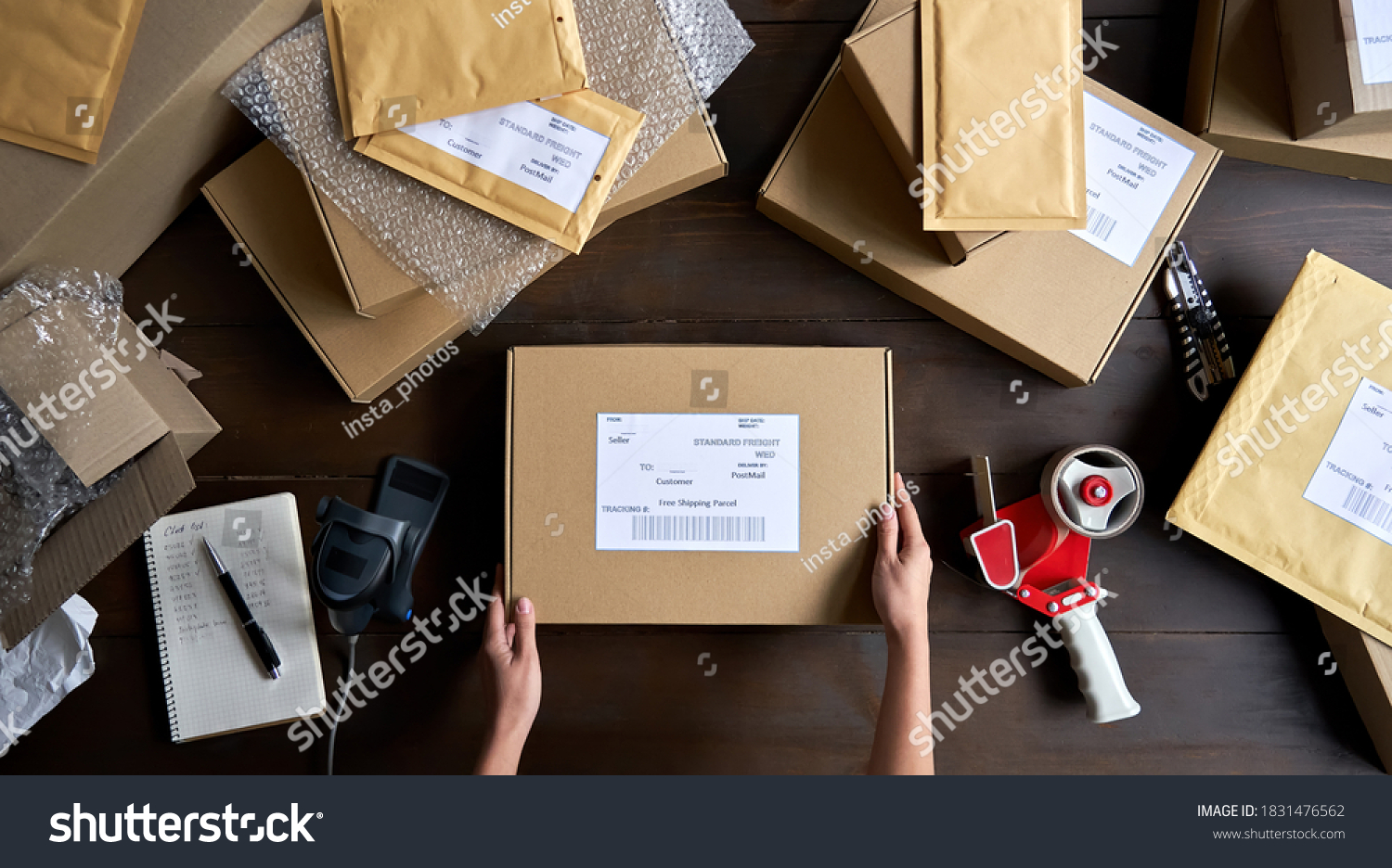 Above table top view of female warehouse worker or seller packing ecommerce shipping order box for dispatching, preparing post courier delivery package, dropshipping shipment service concept. #1831476562