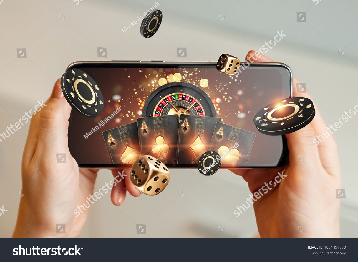 Creative background, online casino, in a man's hand a smartphone with playing cards, roulette and chips, black-gold background. Internet gambling concept. Copy space. #1831491850