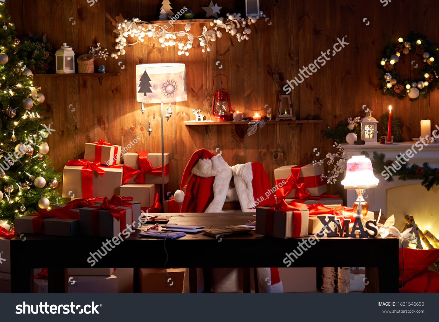 Santa Claus costume and hat hanging on chair at table with Merry Christmas decor gifts presents on holiday eve in cozy Santa home workshop interior late in night with light on xmas tree and fireplace. #1831546690