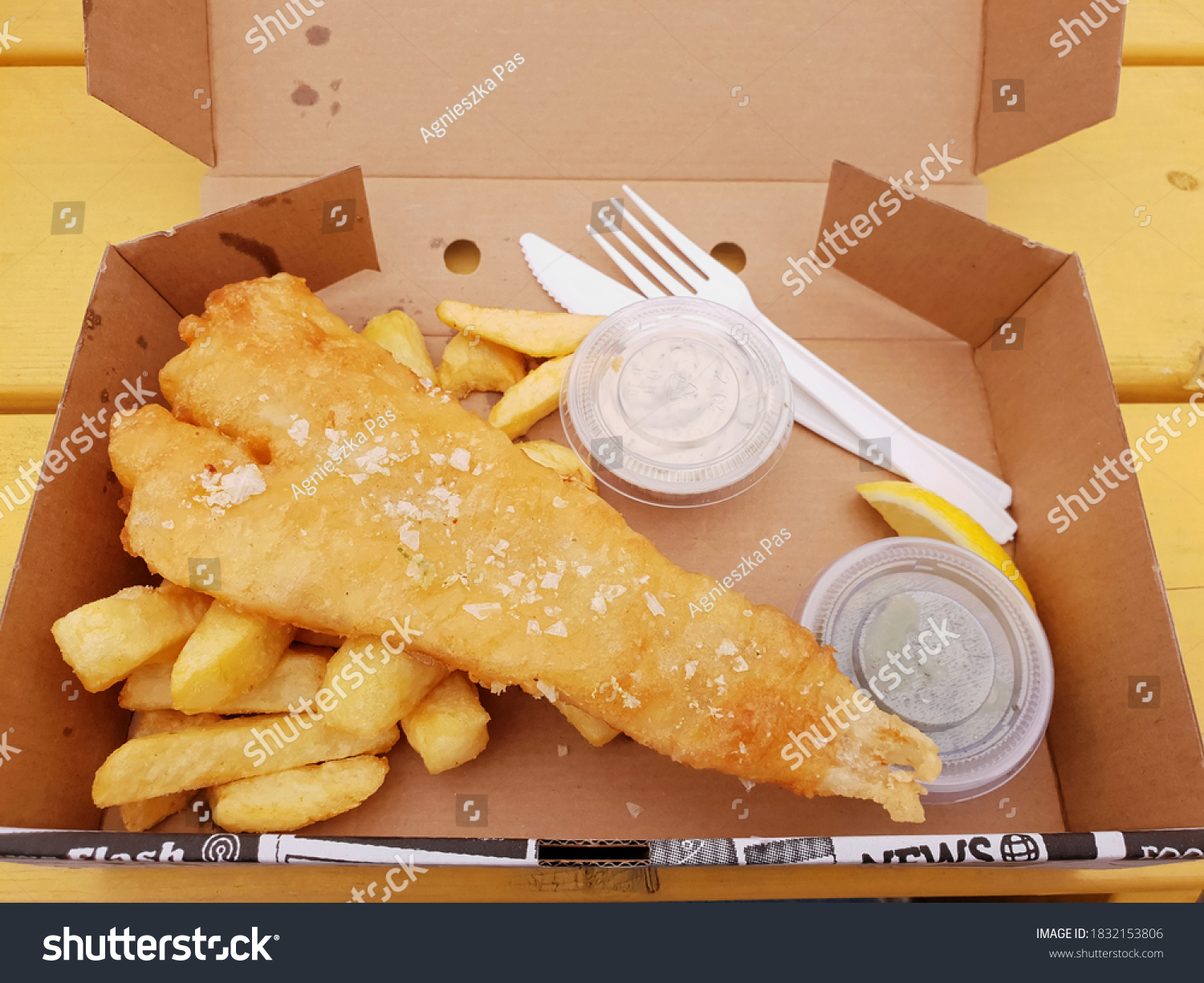 "BRAY, CO. WICKLOW, IRELAND - AUGUST 09, 2020: Close up view of ""Fish and Chips"" meal. Takeaway food in cardboard box, with white plastic cutlery on yellow wooden table. Top view."