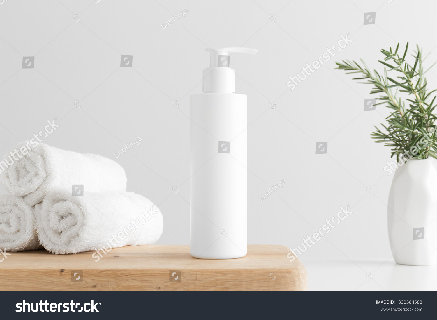 White cosmetic shampoo dispenser bottle mockup with towels and a rosemary  on a wooden table. #1832584588