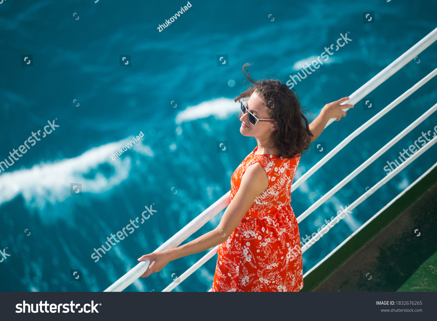 A woman is sailing on a cruise ship, a girl is standing near the fence on a ship and looking at the sea, traveling by ferry, a brunette in a summer dress admires the ocean. #1832676265