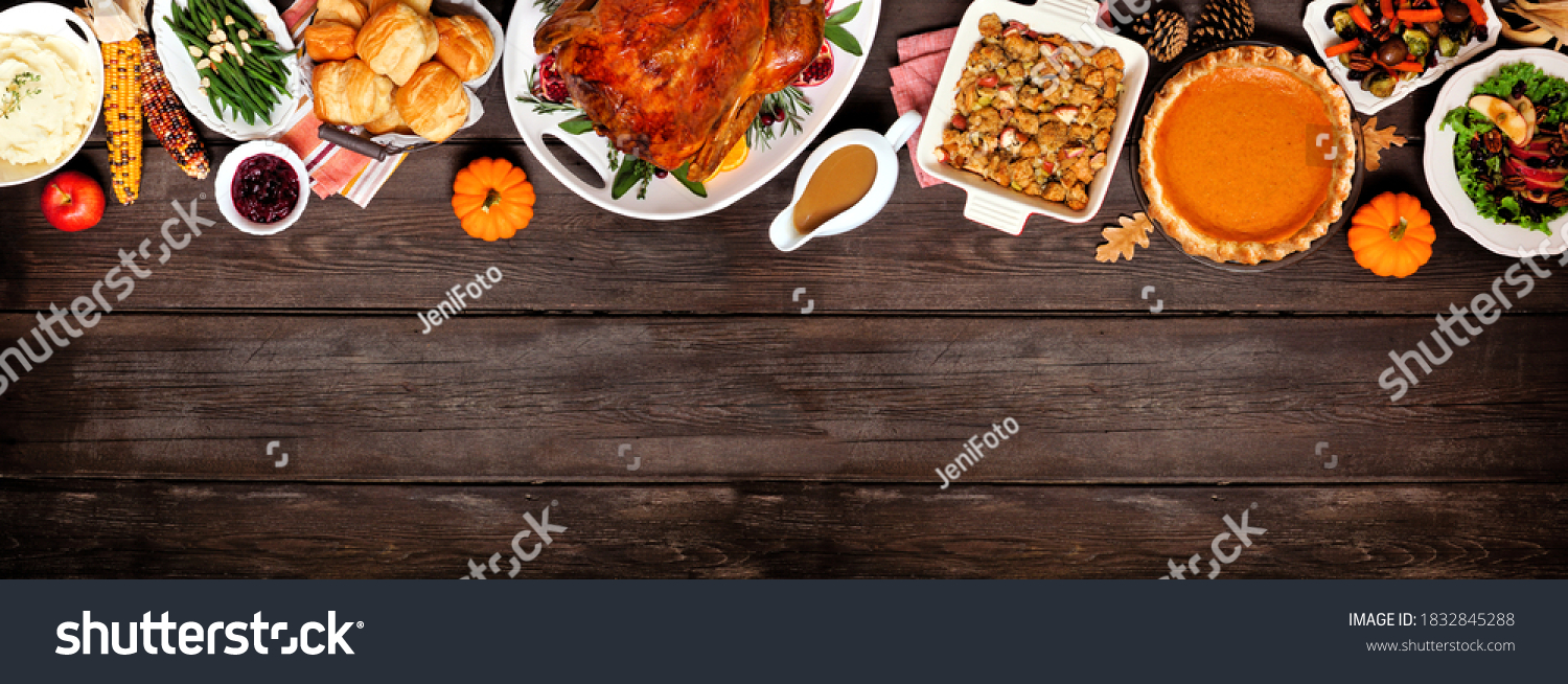 Traditional Thanksgiving turkey dinner. Above view top border on a dark wood banner background with copy space. Turkey, mashed potatoes, dressing, pumpkin pie and sides. #1832845288