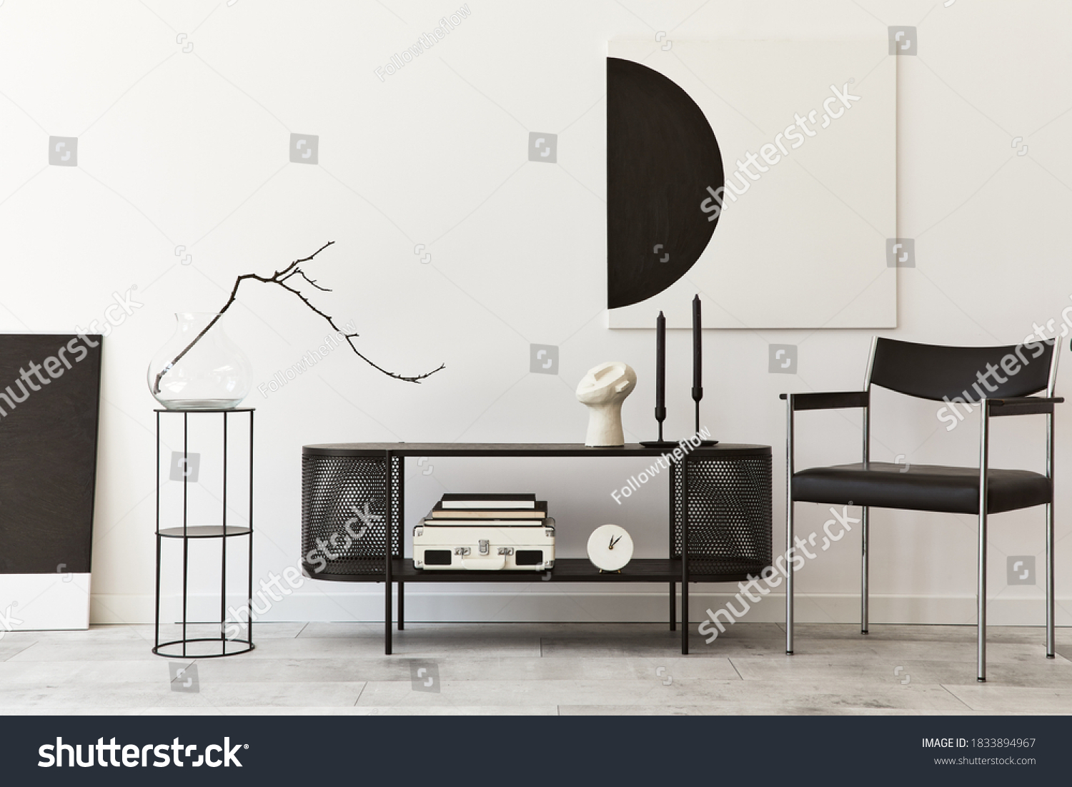 Interior design of modern living room with black stylish commode, chair, mock up art paintings, lamp, book, candlestick, decorations and elegant accessories in home decor. Template. #1833894967