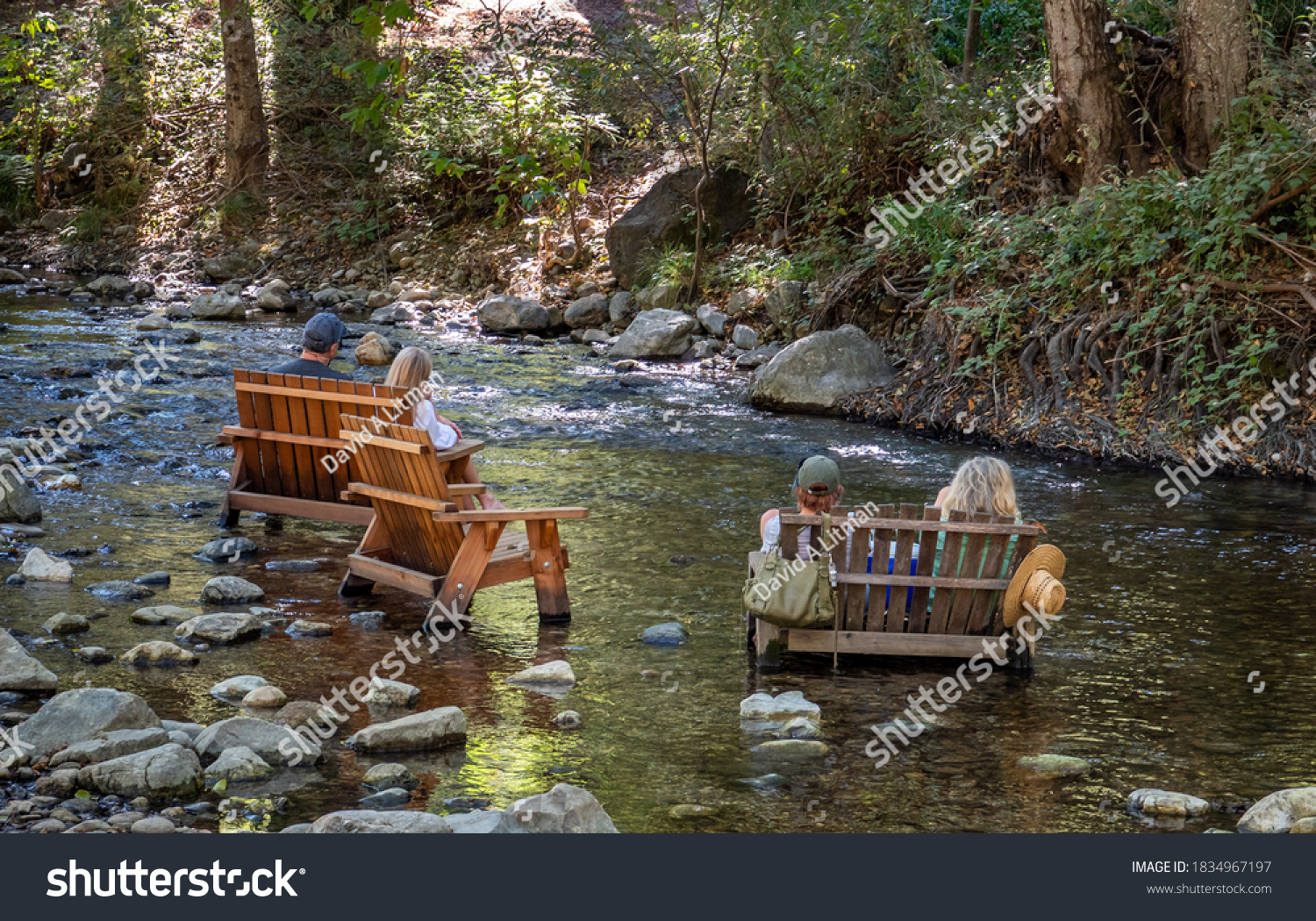 People enjoy the afternoon sitting in wooden chairs placed in the Big Sur River, in California.