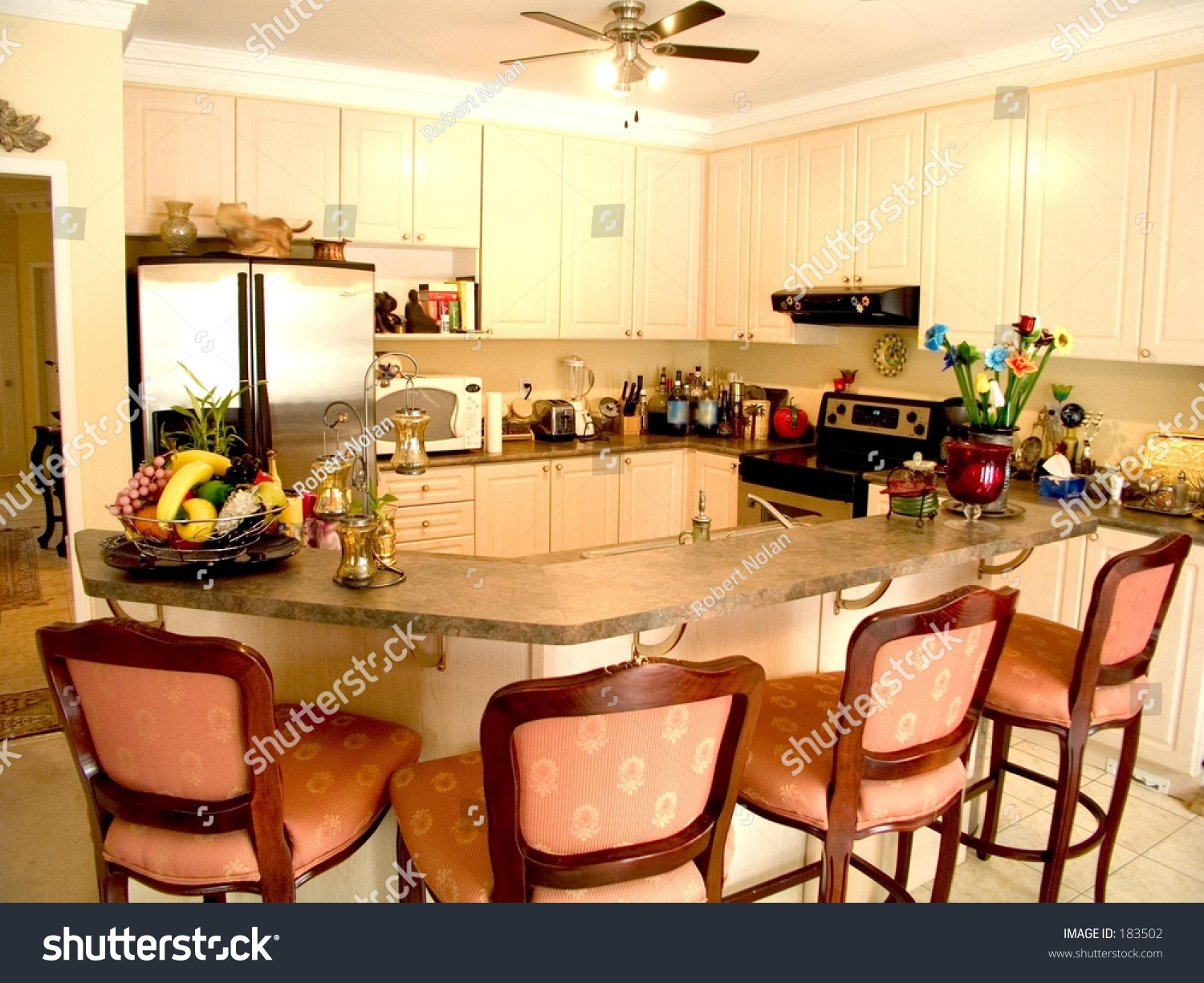 Modern Kitchen With Island Table Four Chairs Fridge Stove And Ceiling Fan Stock Photo 183502