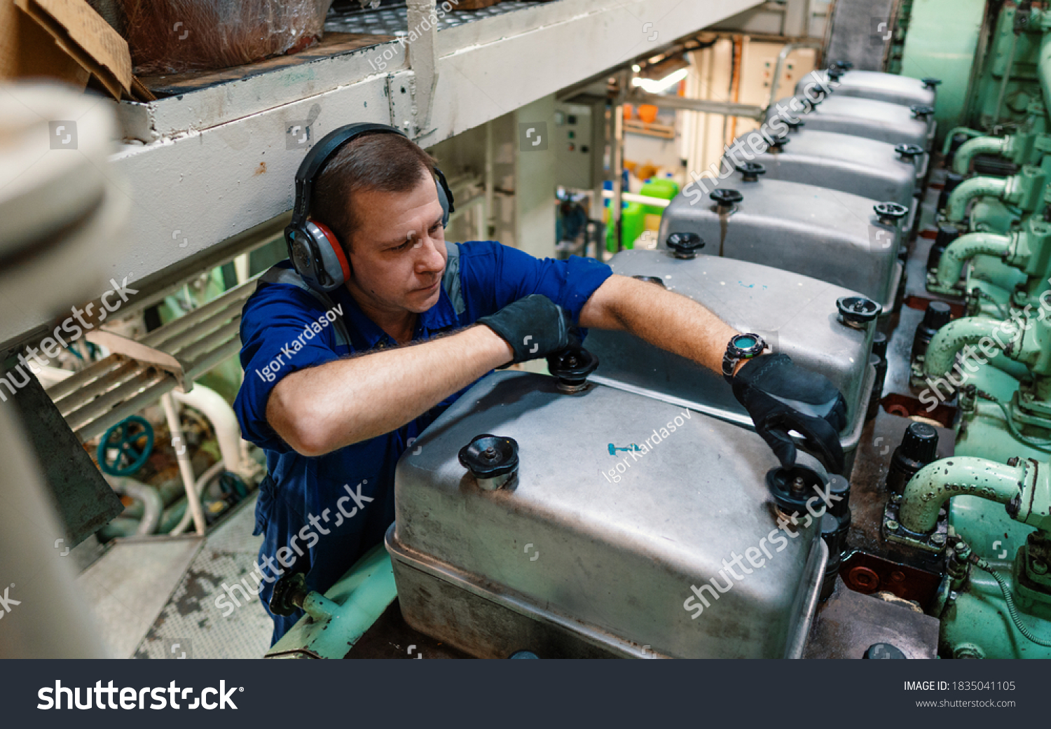 Marine engineer officer reparing vessel engines and propulsion in engine control room ECR. Ship onboard maintenance #1835041105