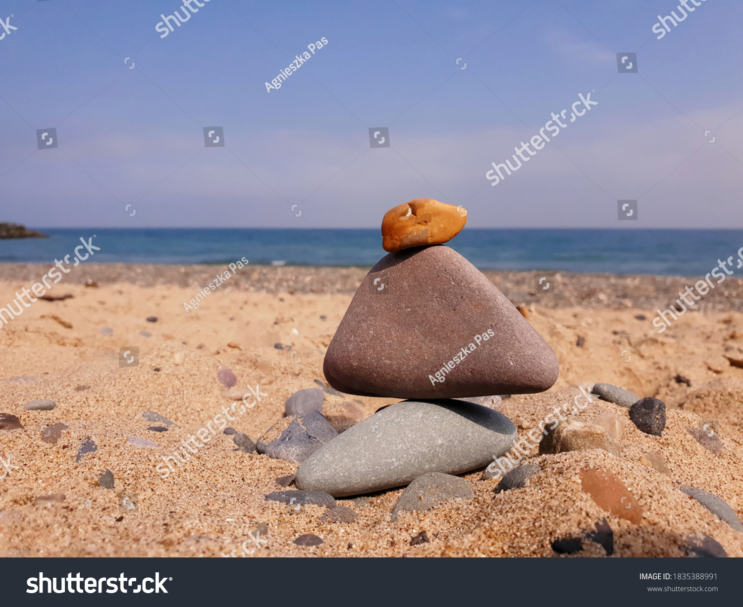 Closeup of a pile of balanced stones on pebble beach with the sea as a blurry background. Sunny summer day.