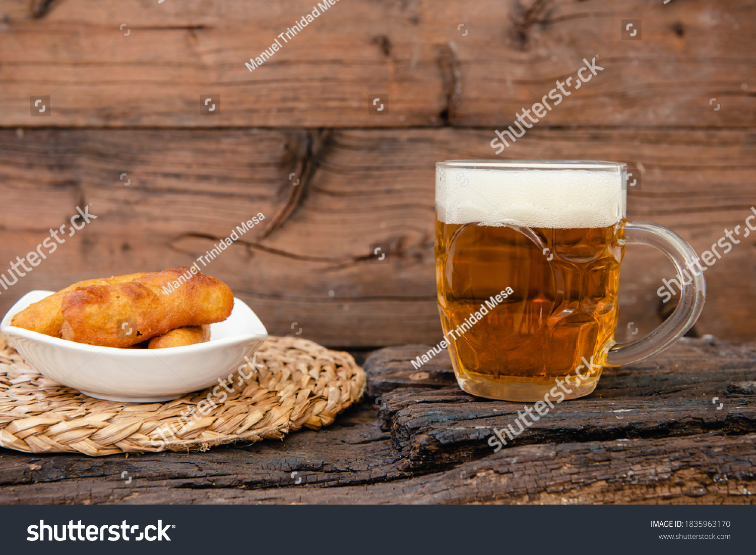 A mug of beer and a snack on rustic background