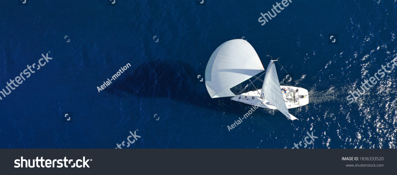 Aerial drone ultra wide panoramic photo of beautiful sail boat with white sails cruising deep blue sea near Mediterranean destination port #1836333520