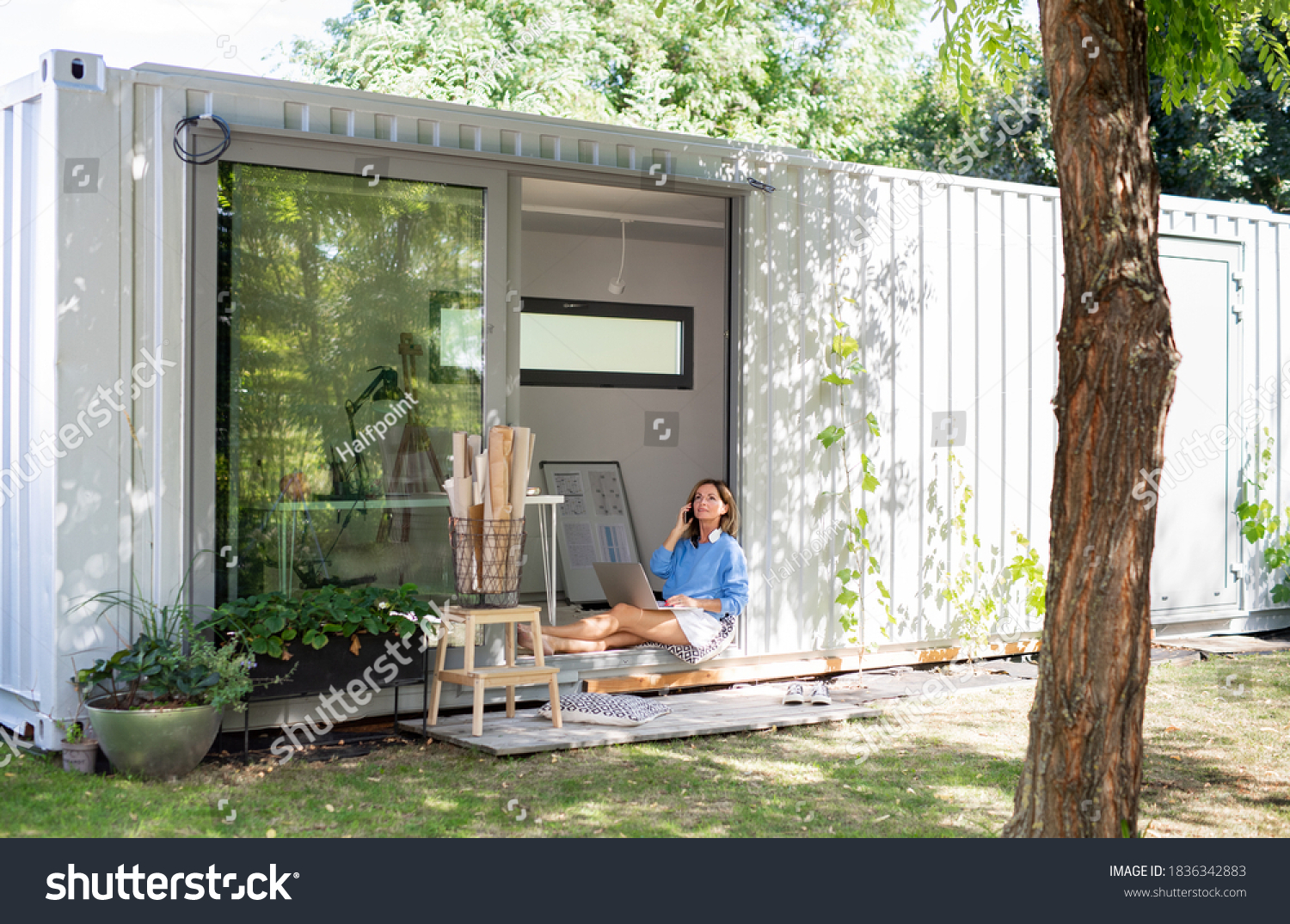 Mature woman working in home office in container house in backyard. #1836342883