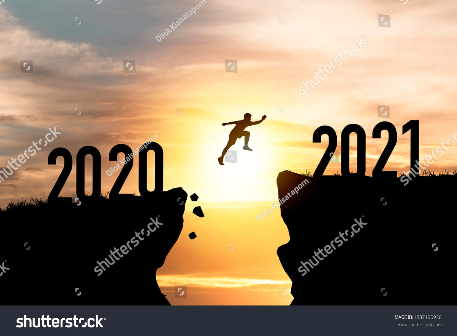 Welcome merry Christmas and happy new year in 2021,Silhouette Man jumping from 2020 cliff to 2021 cliff with cloud sky and sunlight. #1837195936