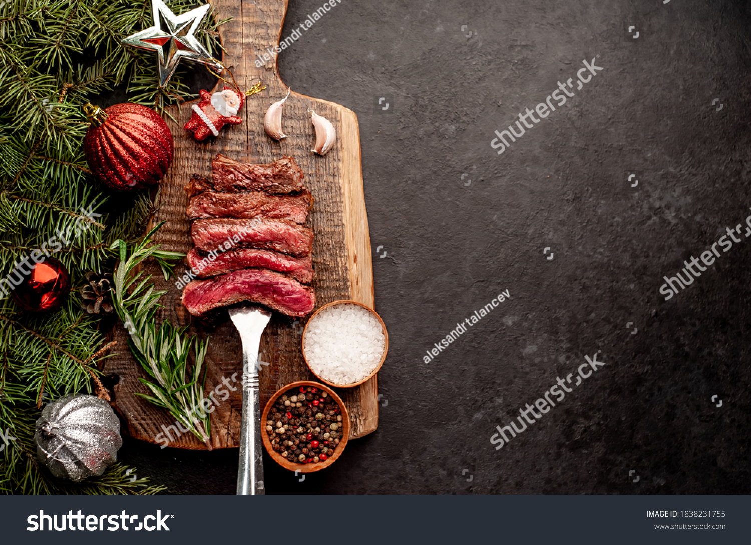 Different degrees of roasting of steak on a meat fork for Christmas on a background of a stone with a spruce and Christmas toys with copy space for your text #1838231755