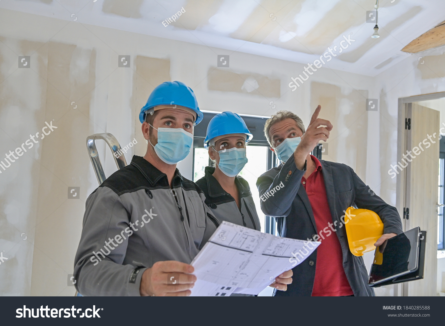 Professional meeting on a construction site between the architect and the craftsmen who wear a protective mask against covid-19 #1840285588