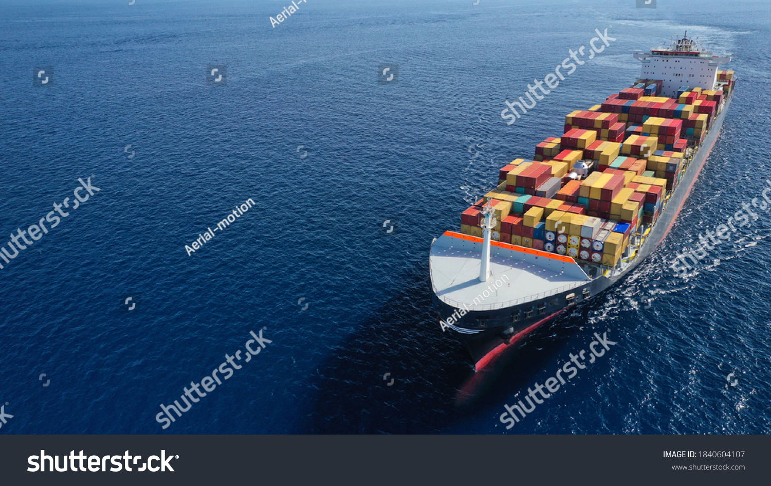 Aerial drone photo of huge container tanker ship carrying truck size colourful containers in deep blue open ocean sea #1840604107