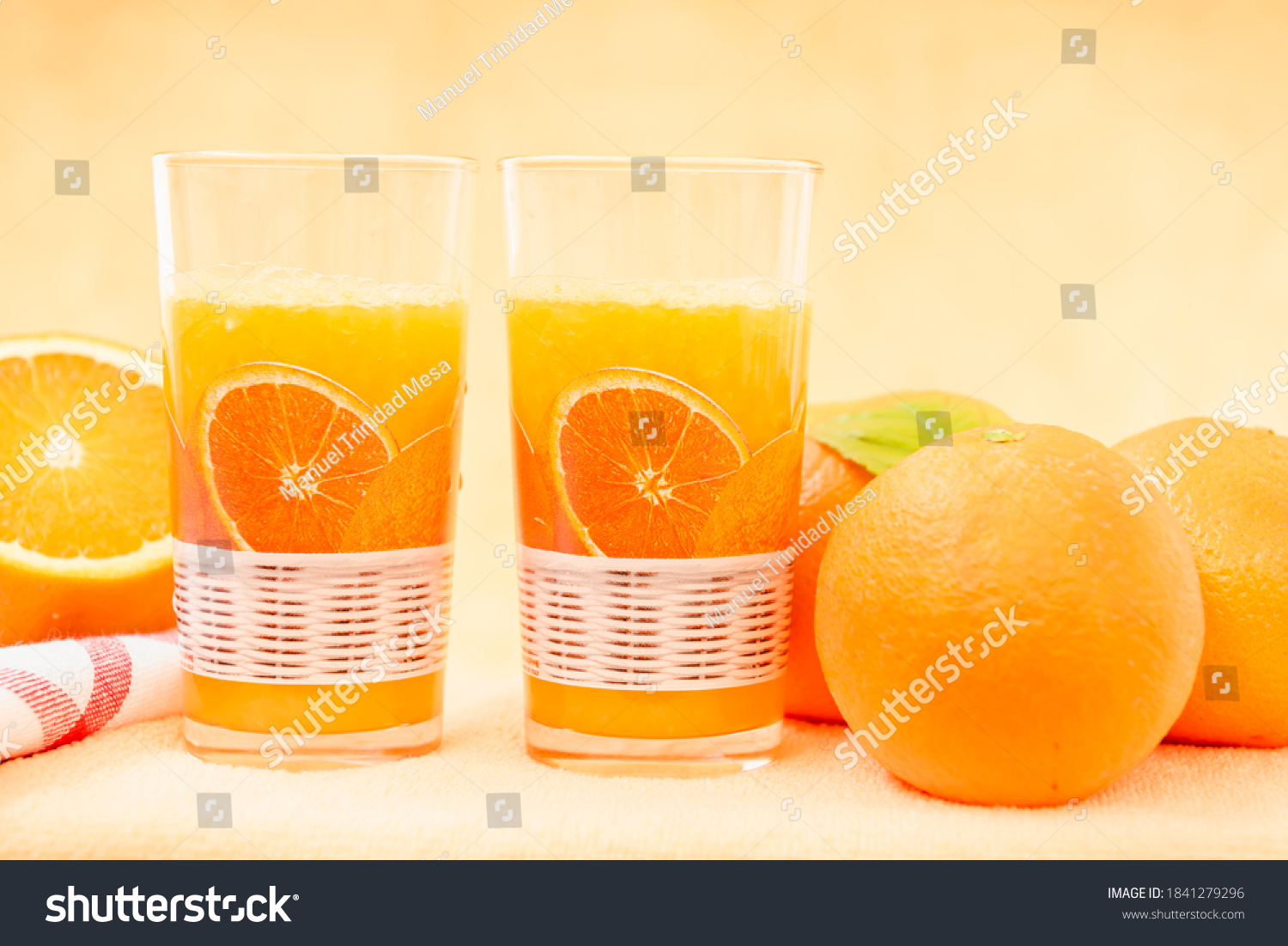Two glasses of orange juice and fresh oranges on the table