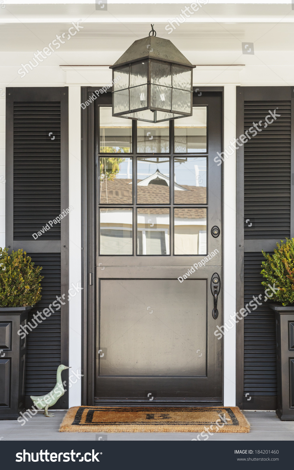 Royalty free a black front door to a white home with for Duck house door size