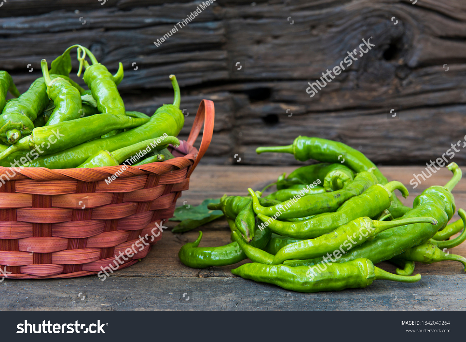 Green peppers in a basket and on the table, rustic wooden background