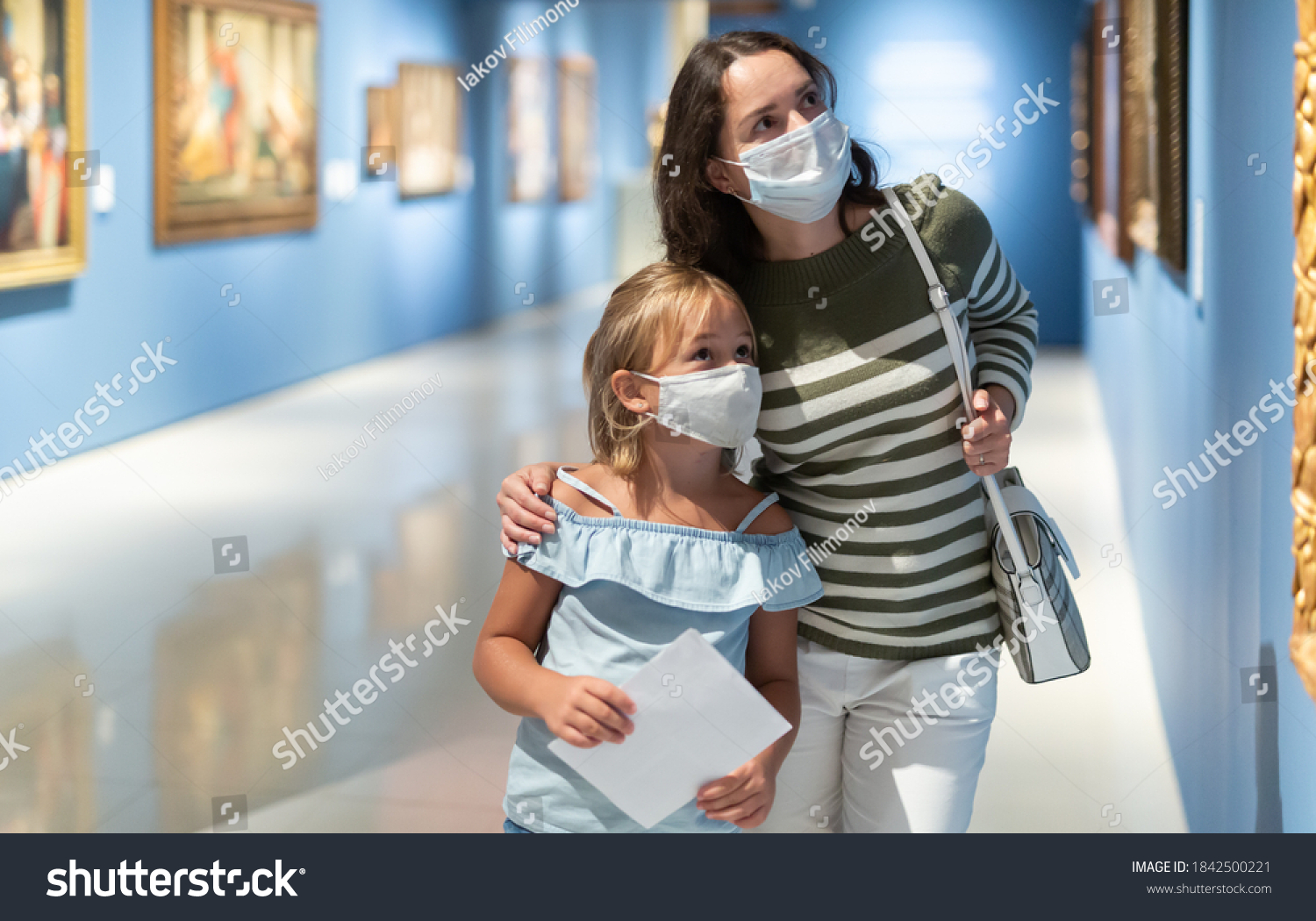 Portrait of woman with girl in medical masks standing in museum of art and looking at painting #1842500221