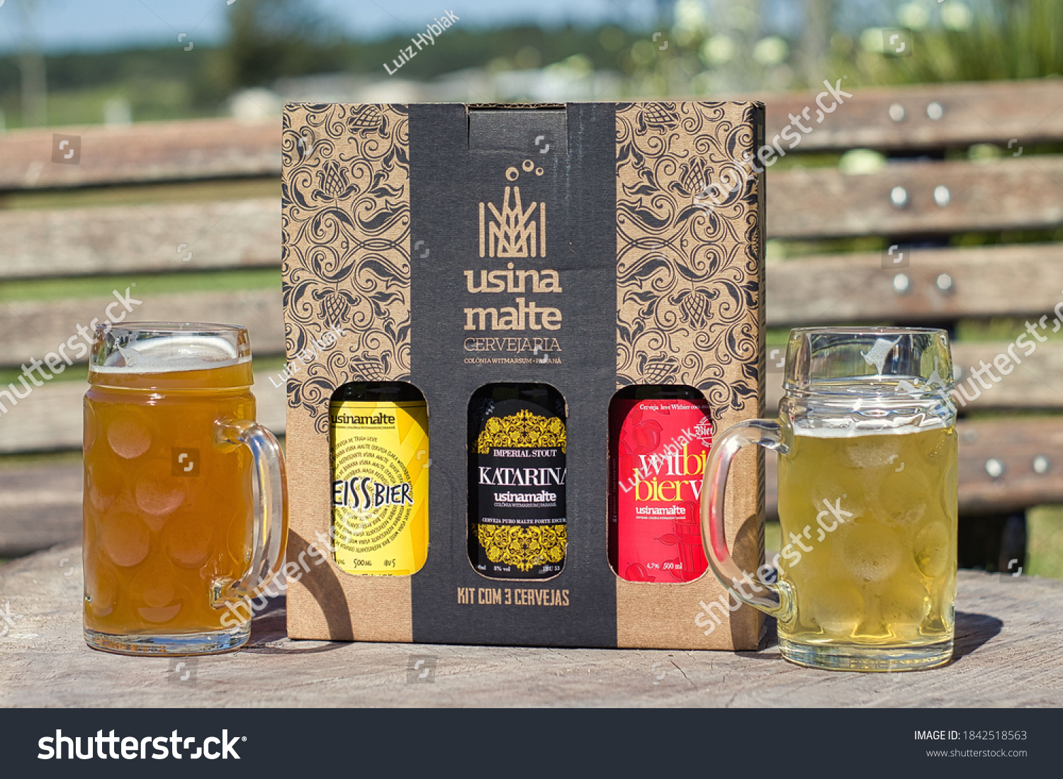 "Palmeira, Paraná, Brazil - August 29, 2020. ""Usina Malte"" Brewery located at ""Colônia Witmarsum"". A box containing three different beers, two partially filled beer glasses. Wood bench in background."