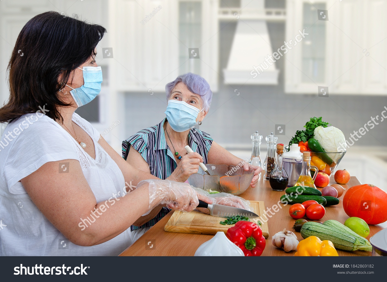 Even the pandemic could not cancel the weekly joint cooking of a vegetable salad by a caregiver and old lady. Only both are wearing protective face masks now. #1842869182