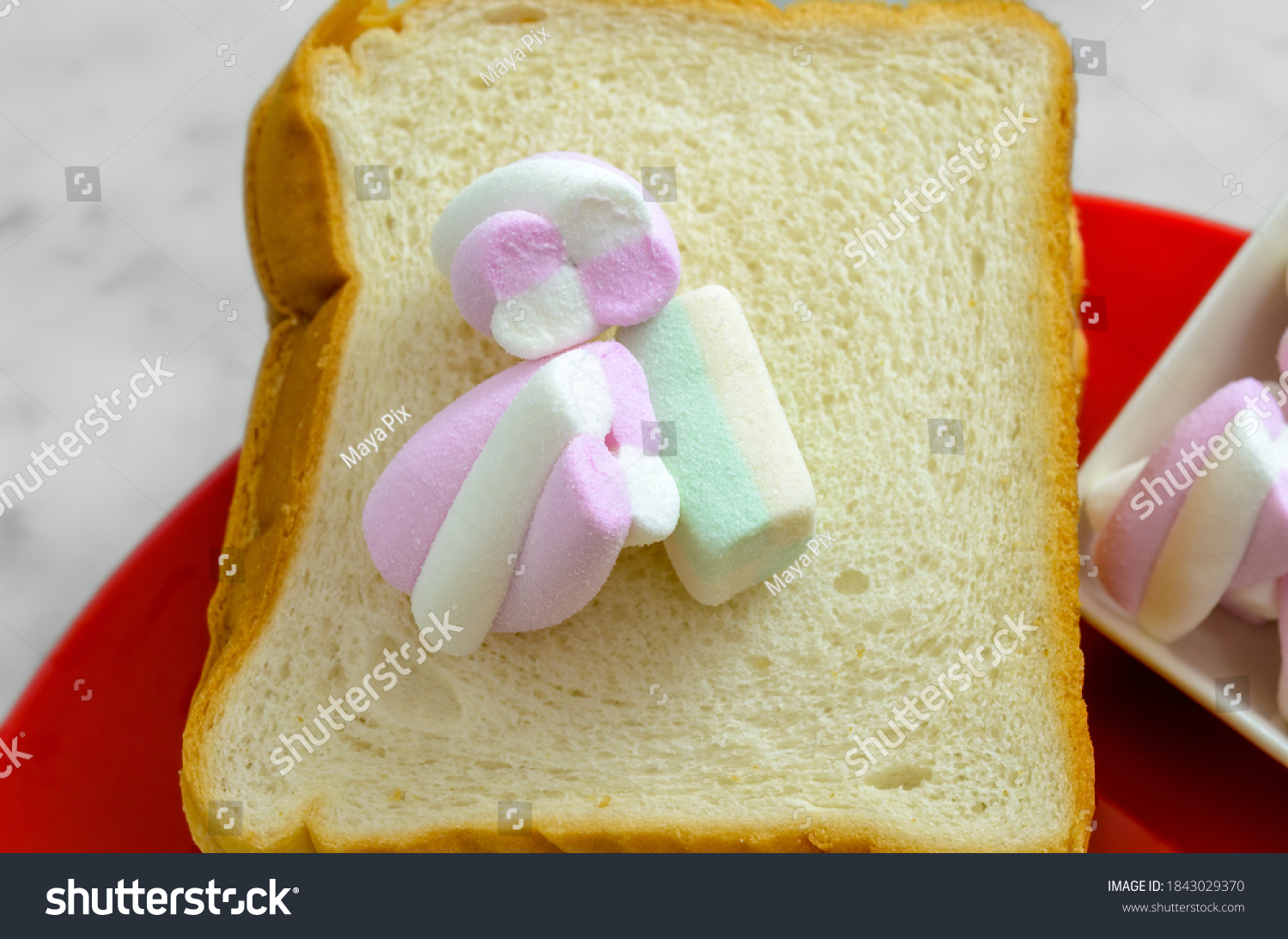 Pastel Colored Marshmallows on a slice of Bread ready to be sandwiched.