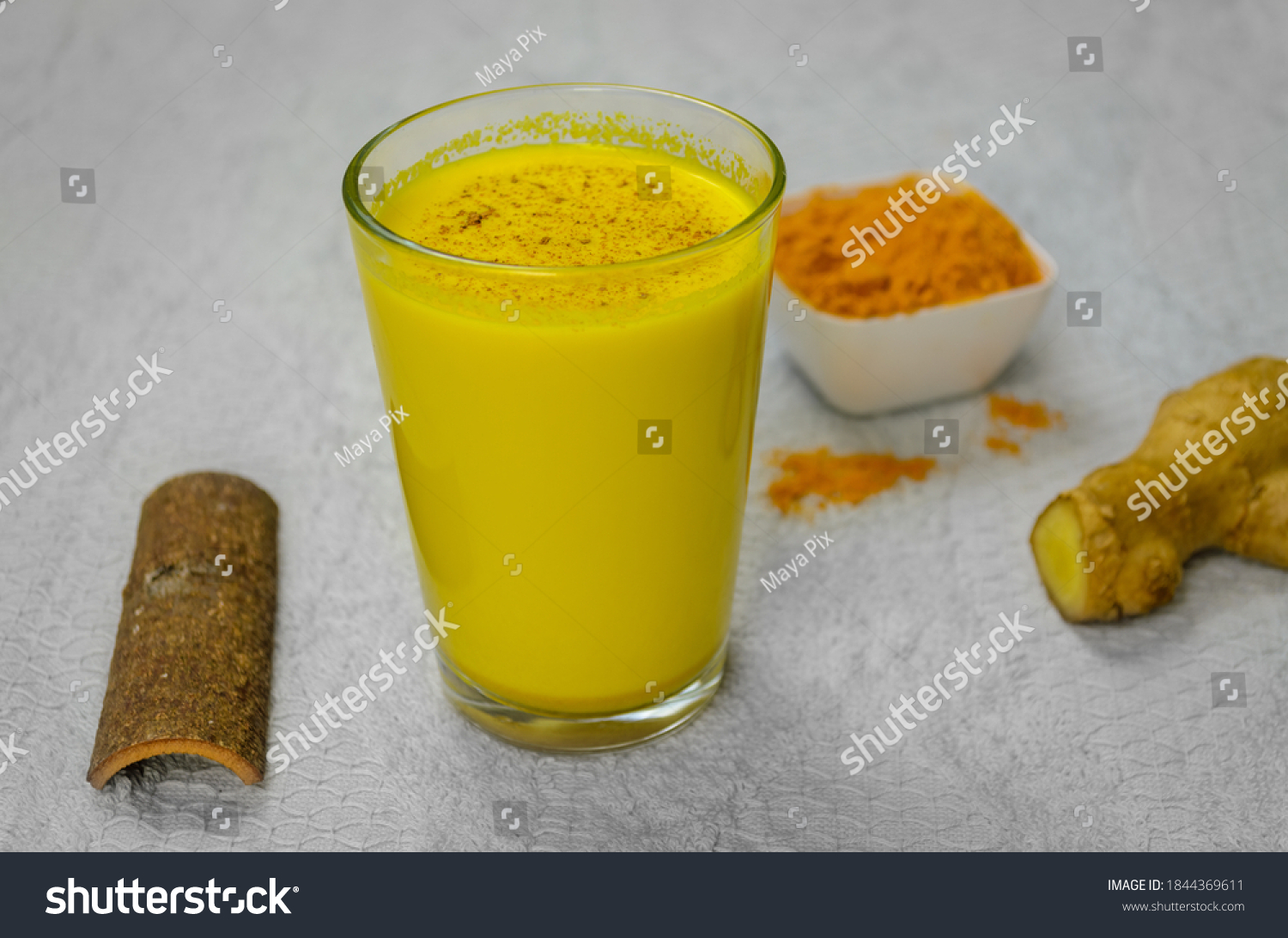 Closeup of Immunity Boosting Turmeric Milk along with cinnamon, turmeric powder and ginger