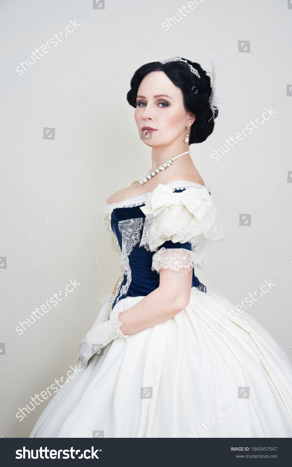 A beautiful elegant dark haired woman in a historic 1867 coronation dress on a white background looks at the camera #1845957547